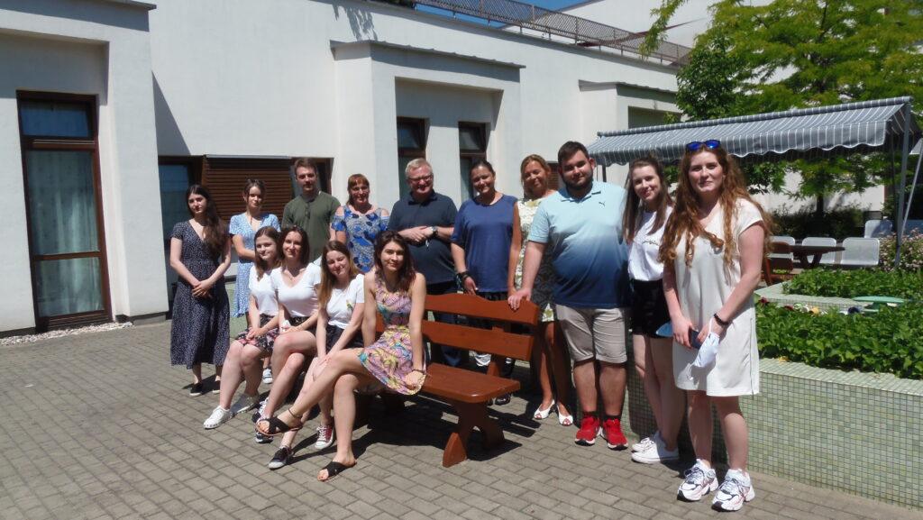 grupa studentów i pracowników Centrum Alzheimera znajduje się na słonecznym patio. Cztery studentki siedzą na ławce, pozostałe osoby stoją za nimi. W tle widać budynki oraz zieleń i parasol przeciwsłoneczny