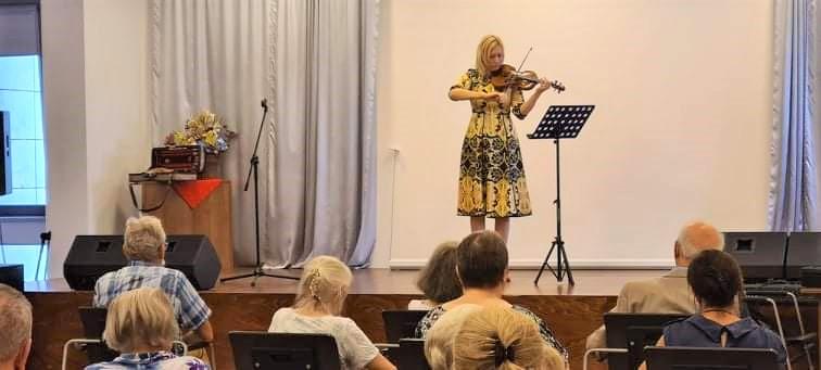 : Na scenie stoi skrzypaczka w żółto – czarnej sukience. Poniżej widzowie słuchający koncertu.
