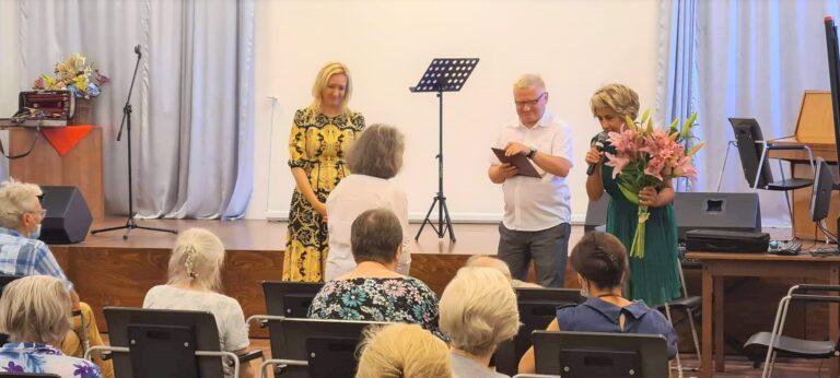 Dyrektor Centrum Alzheimera (mężczyzna)oraz zastępca dyrektora Centrum Alzheimera (kobieta) wręczają skrzypaczce dyplom z podziękowaniami za występ oraz bukiet kwiatów. Przed nimi siedzą widzowie.